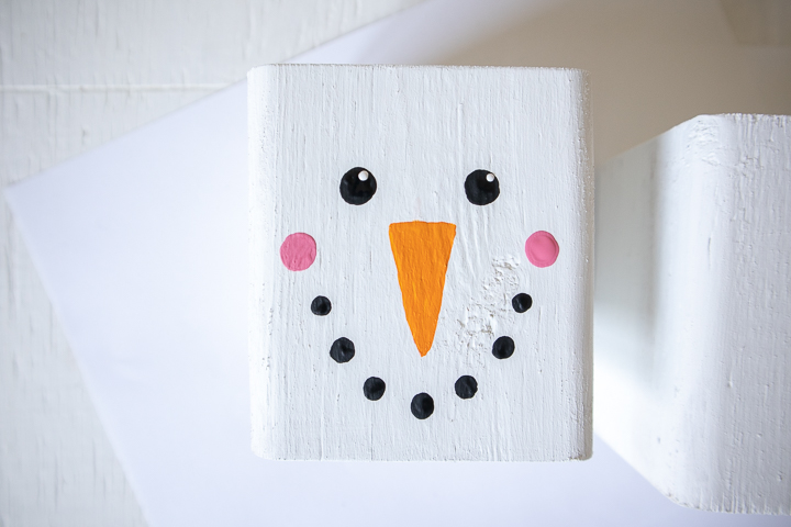 Adding to small dabs of white paint to the black circle snowman eyes.