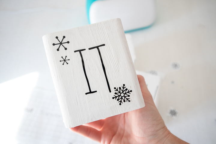 """Wood block with snowflake images and the word """"it."""""""