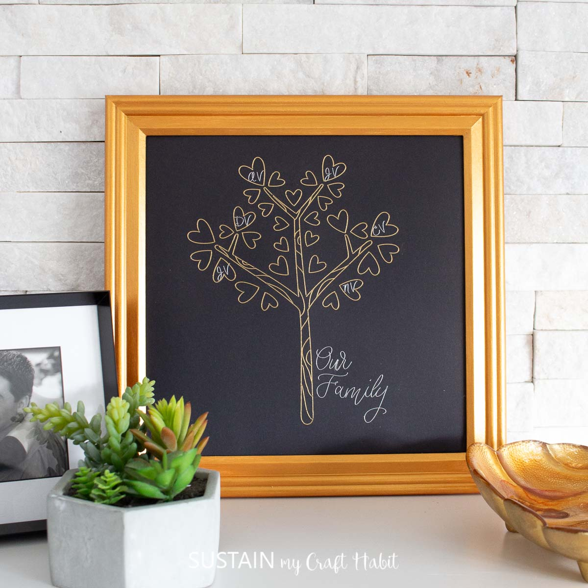 Framed family tree craft resting on a white surface, leaning against a white brick background.