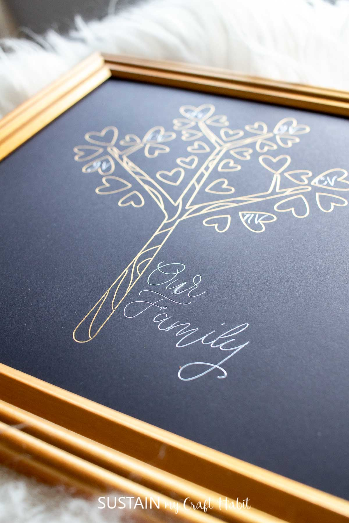 "Close up view of the words ""our family"" applied to black cardstock paper with silver Cricut foil."