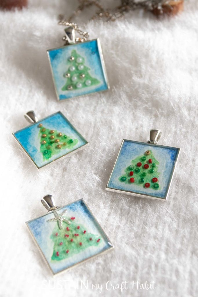 Four Christmas tree resin pendants laid on a soft white background.