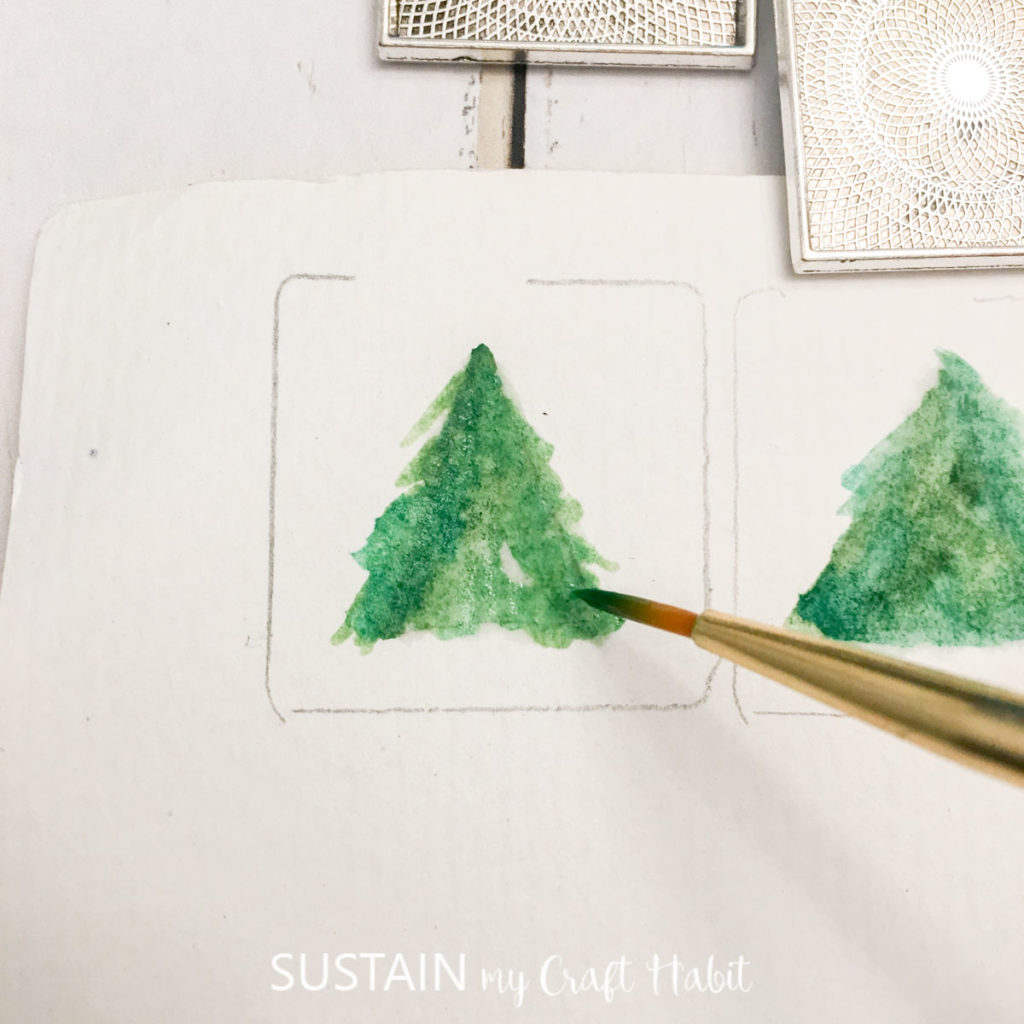 Painting a green tree on the traced paper.