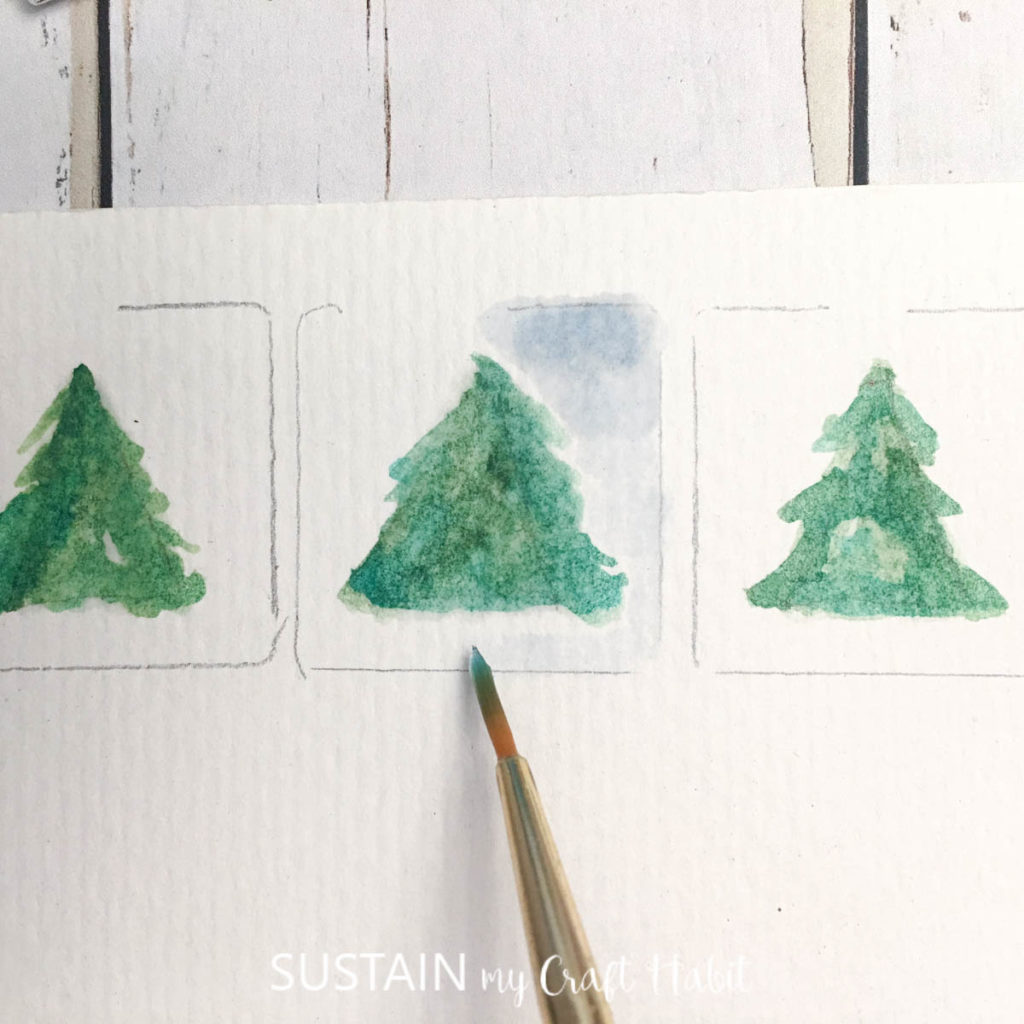 Painting a blue background around the green tree.