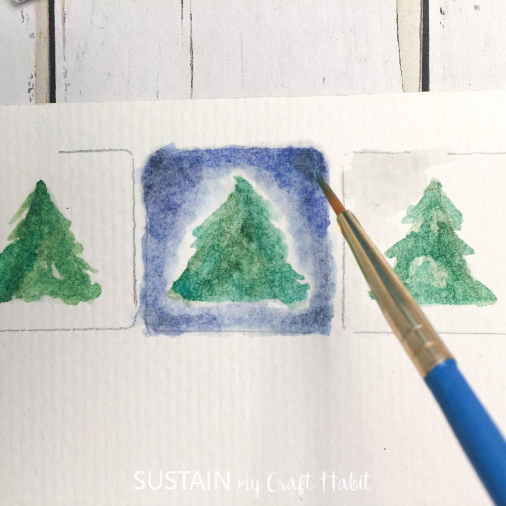 Adding more blue paint around the green tree.