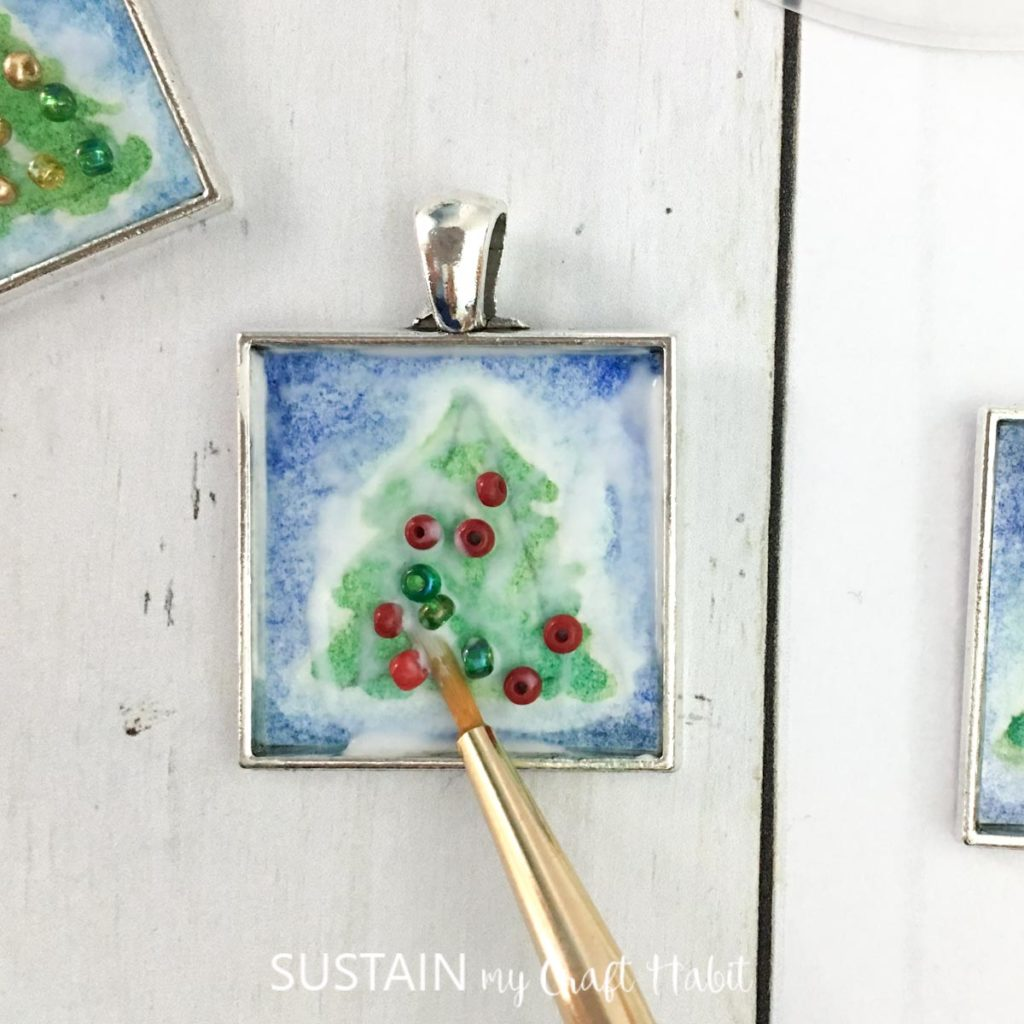 Gluing small beads to the green painted tree.