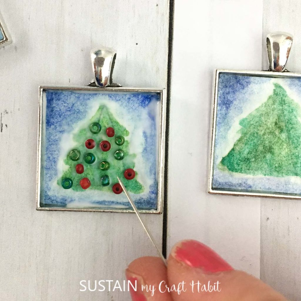Using a tooth pick to move beads on the green painted tree.