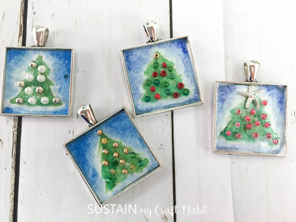 Decorated bezel charms with painted Christmas trees and beads.