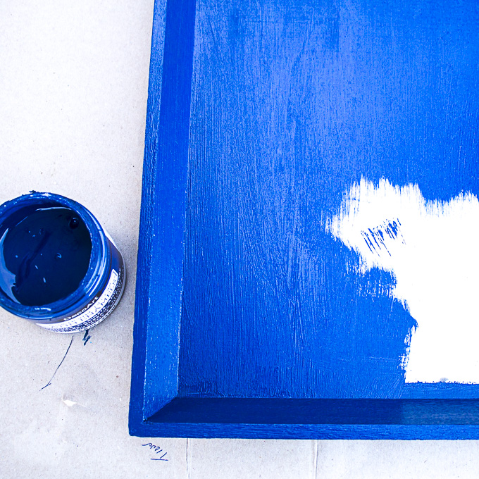 Painting a wood tray blue.
