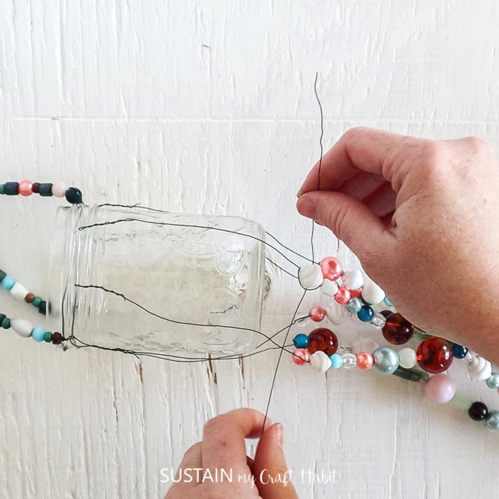 wrapping a piece of wire around the top of the beaded strands just under the mason jar.