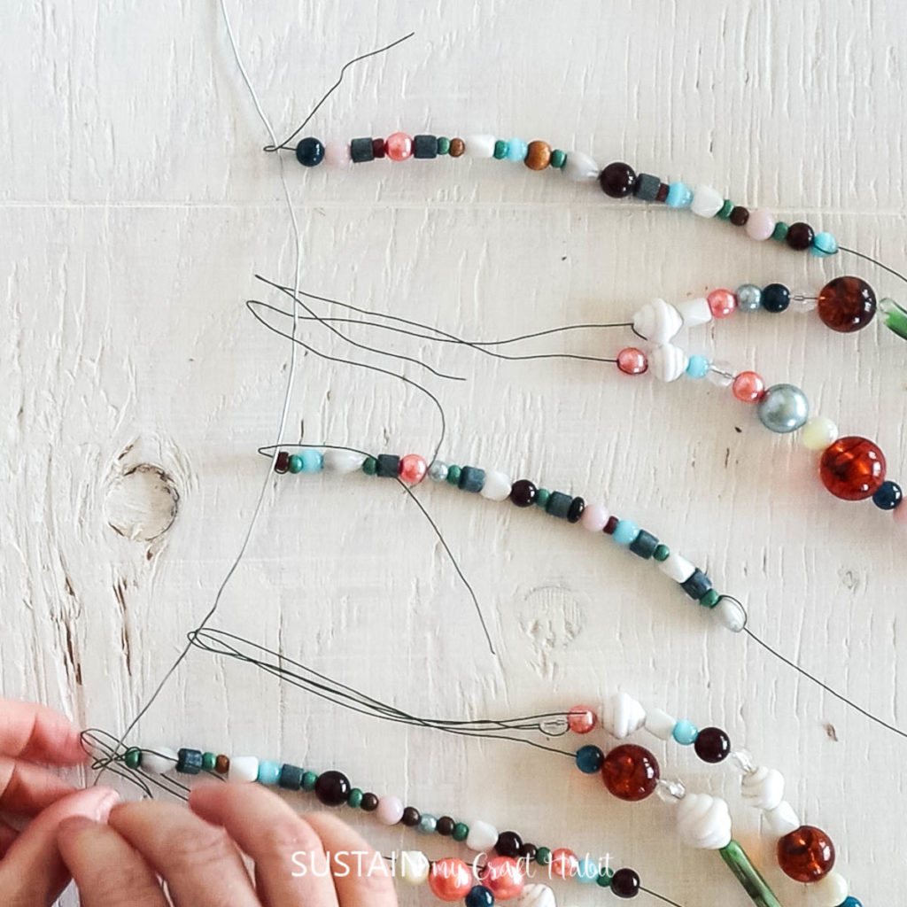 Folding the ends of the beaded floral wire around silver wire.