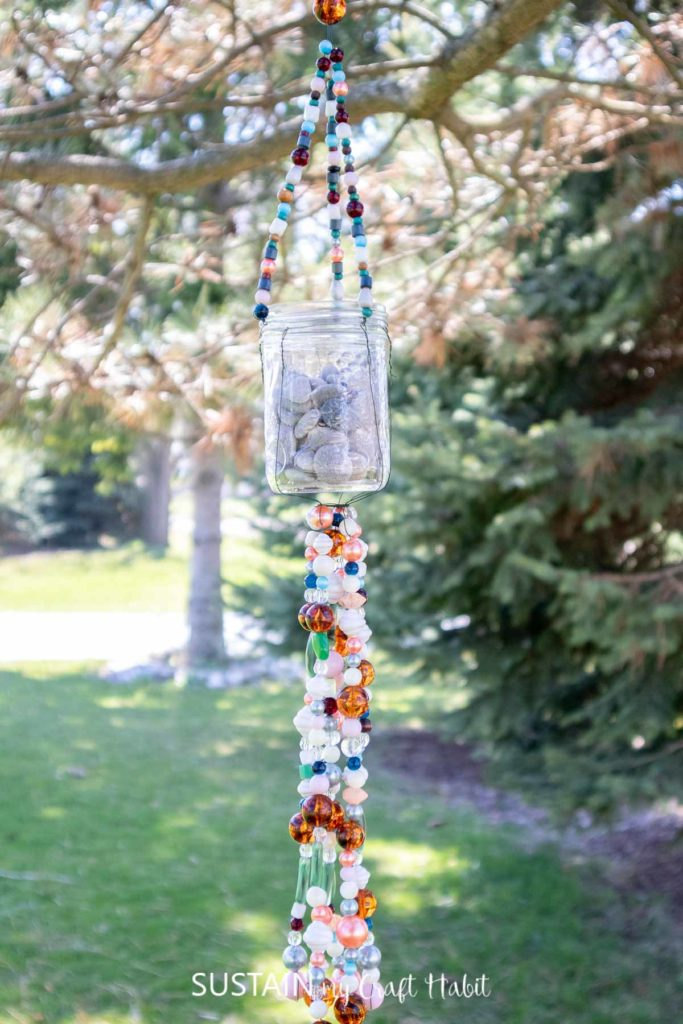 Hanging mason jar wind chime made with beads and wire.