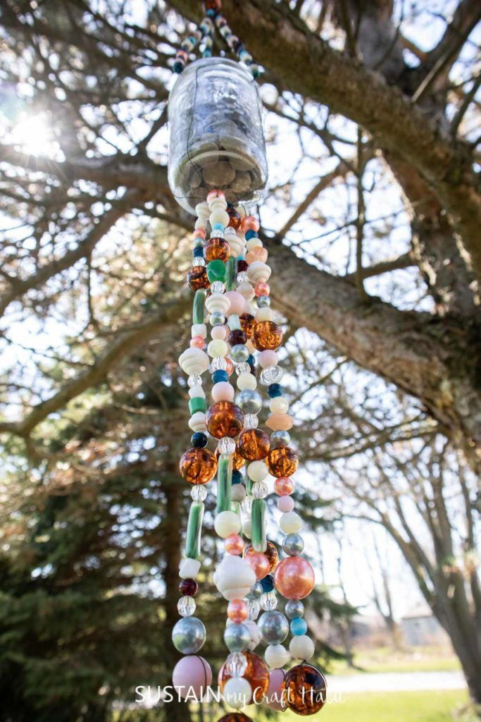 Wind chime made with a mason jar and beads hanging from a tree branch.