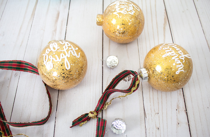 Reattaching the ornament caps on the glittering gold painted glass ornaments.