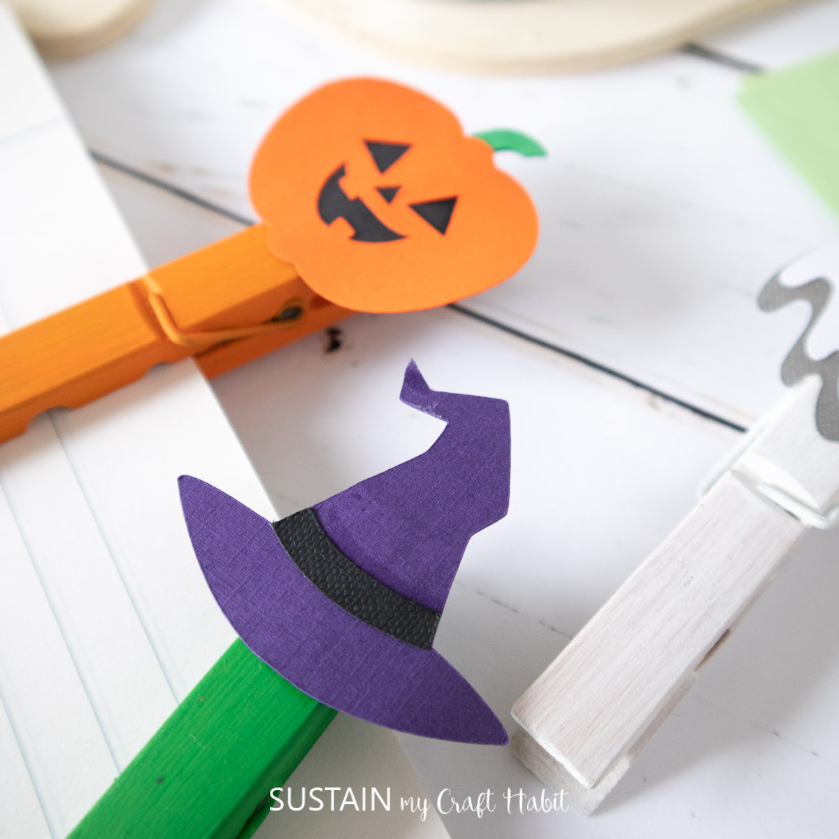 Completed pumpkin and witch's hat clothespin crafts being used to hold papers together.