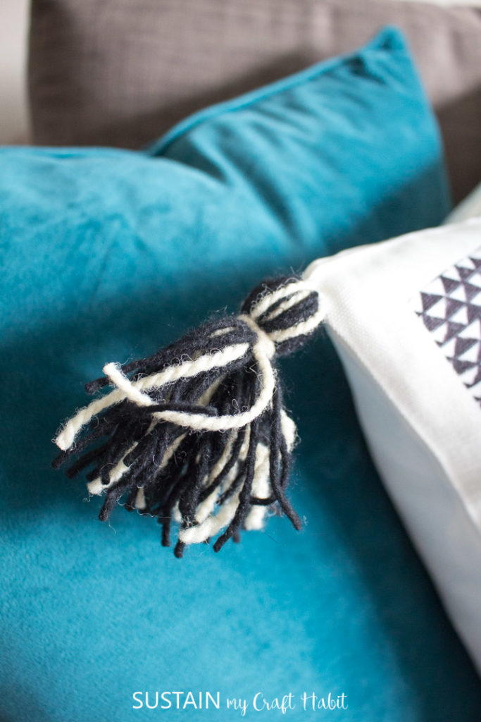 Attaching the tassel to a throw pillow.