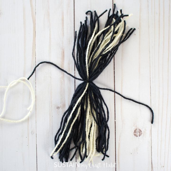 tying the strand of yarn around the mixed yarn.