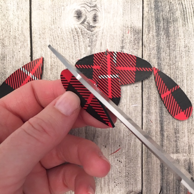 Using scissors to trim extra gift wrap from the wood cut out.