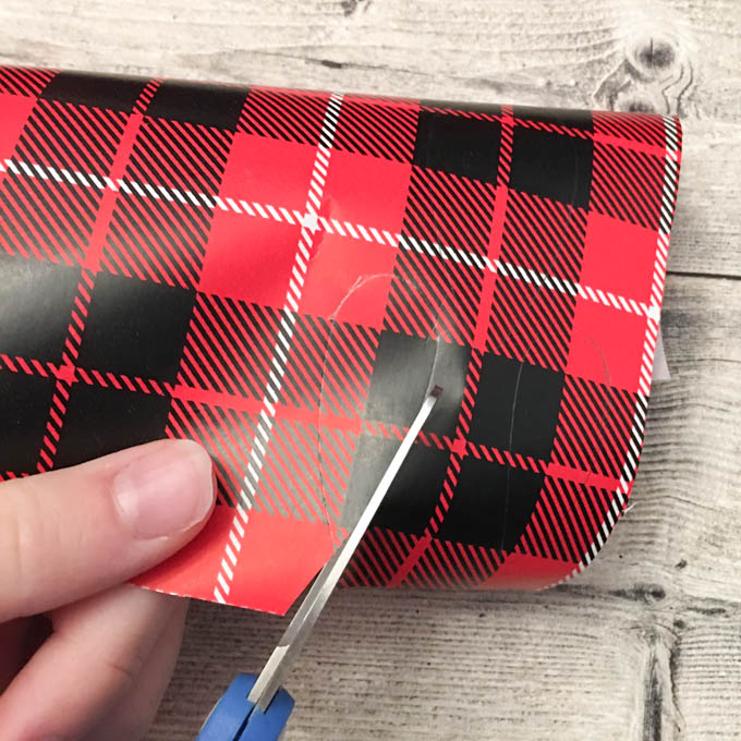 Cutting out the traced shapes on the plaid gift wrap.