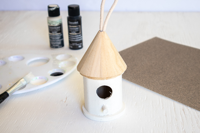 Painting the wooden birdhouse white.