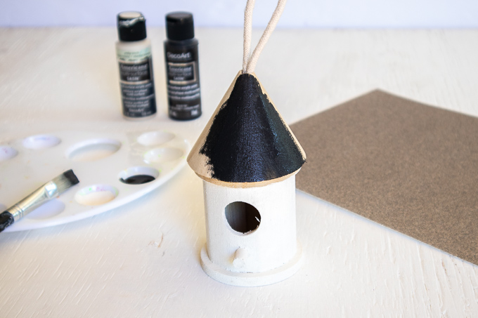 Painting the wooden birdhouse roof black.