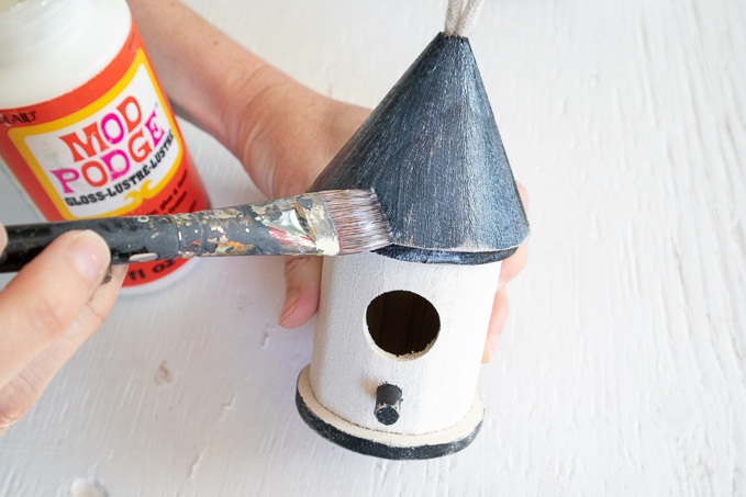 Applying mod podge over the surface of the birdhouse.