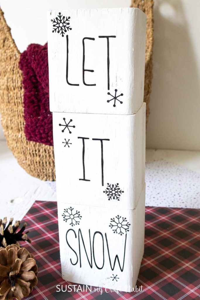 """Back of the wood blocks with letters stacked to say """"let it snow."""""""