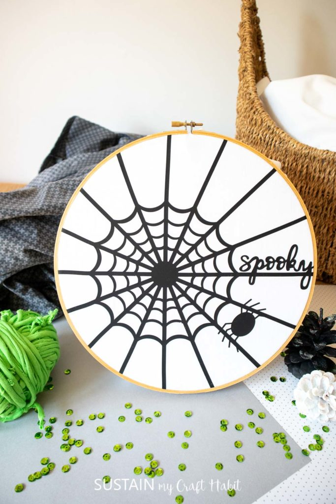 completed spider web art styled with green adn black accessories