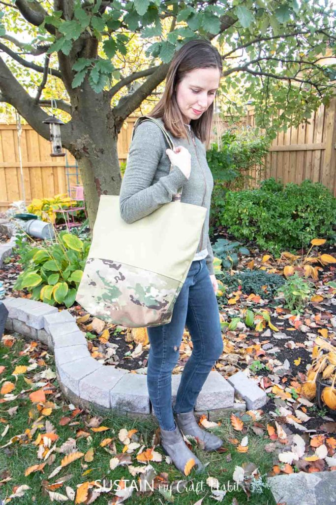 holding large camo tote bag outside in the Fall