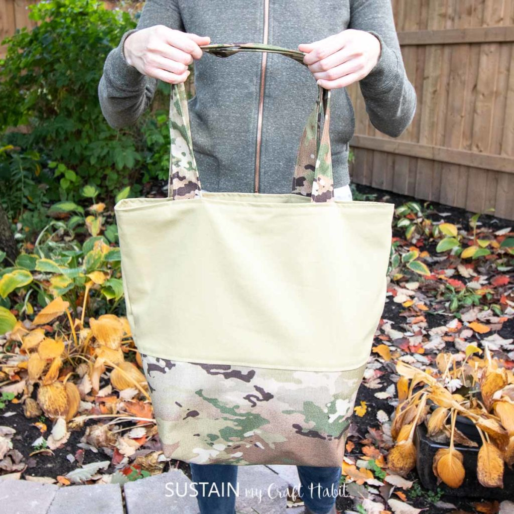 showing off a large two-fabric camo tote bag with a reinforced base with coated camouflage material and the upper panel in cotton canvas