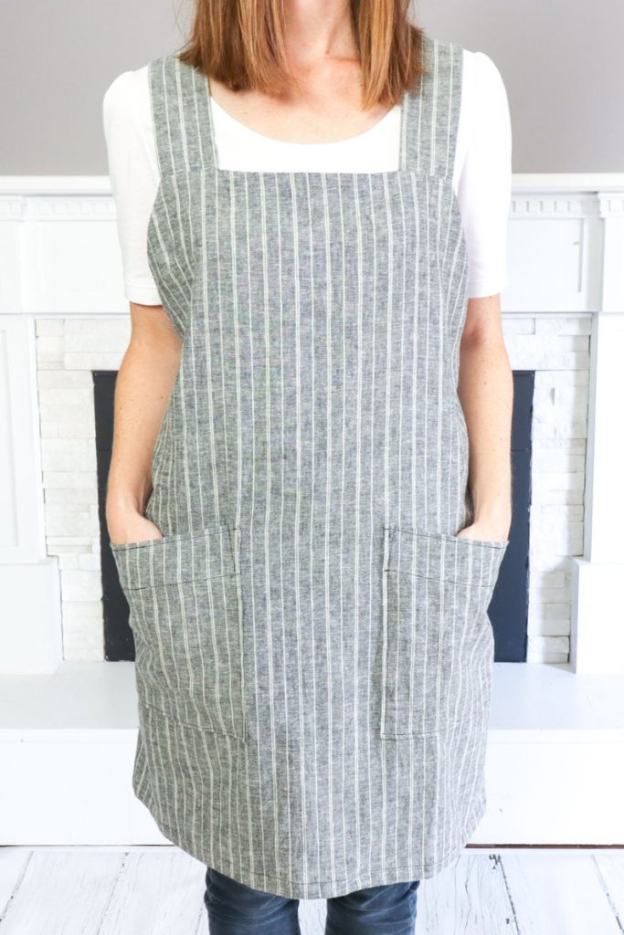 Wearing a striped square neck apron.