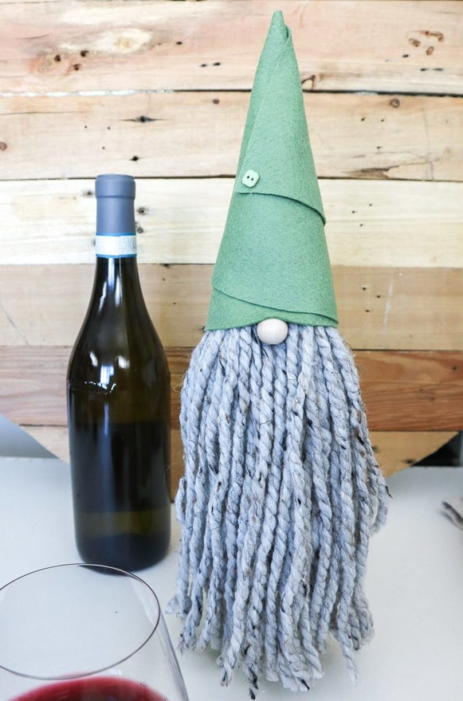 Gnome wine bottle toppers next to a wine bottle.