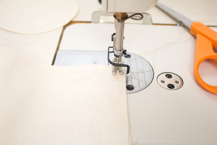 Sewing the canvas fabric to form a tube shape.