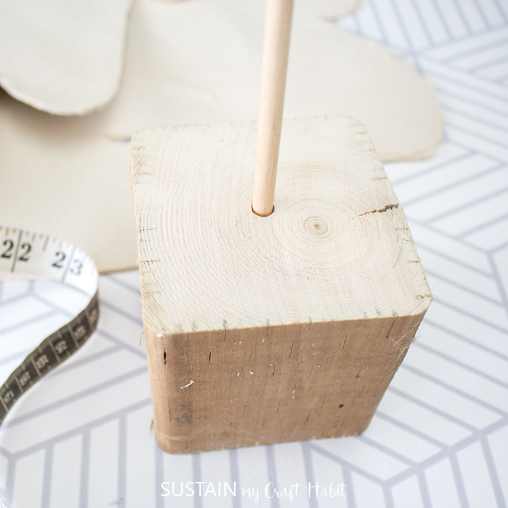 Inserting the wooden dowel into the wooden block.