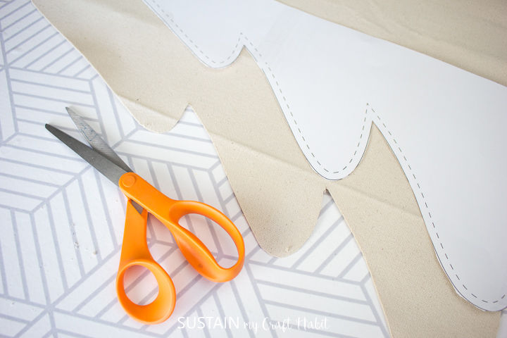 Cutting out the Christmas tree pattern from the canvas.