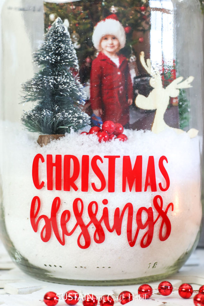 Placing a photograph, Christmas brush trees and reindeer cutouts inside the pickle jar terrarium.