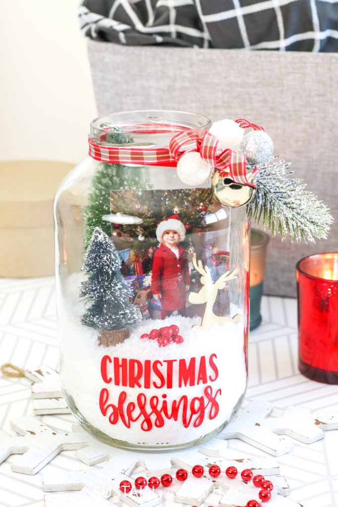 Pickle jar Christmas terrarium with decorative ribbon, Christmas accessories, fake snow and a picture.