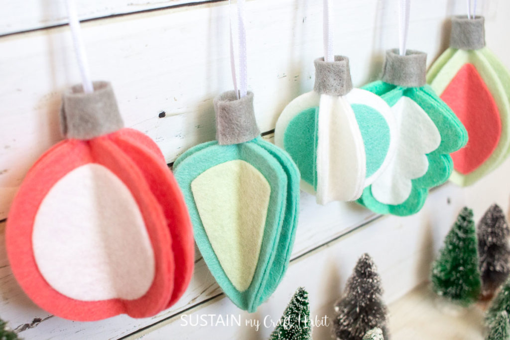 Retro inspired 3D felt Christmas ornaments hanging next to a wall.