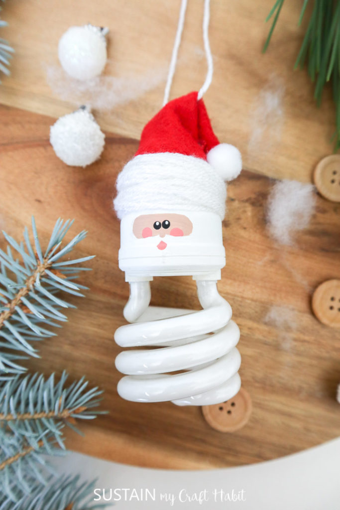 Overhead view of a light bulb Christmas ornament that looks like Santa Claus.