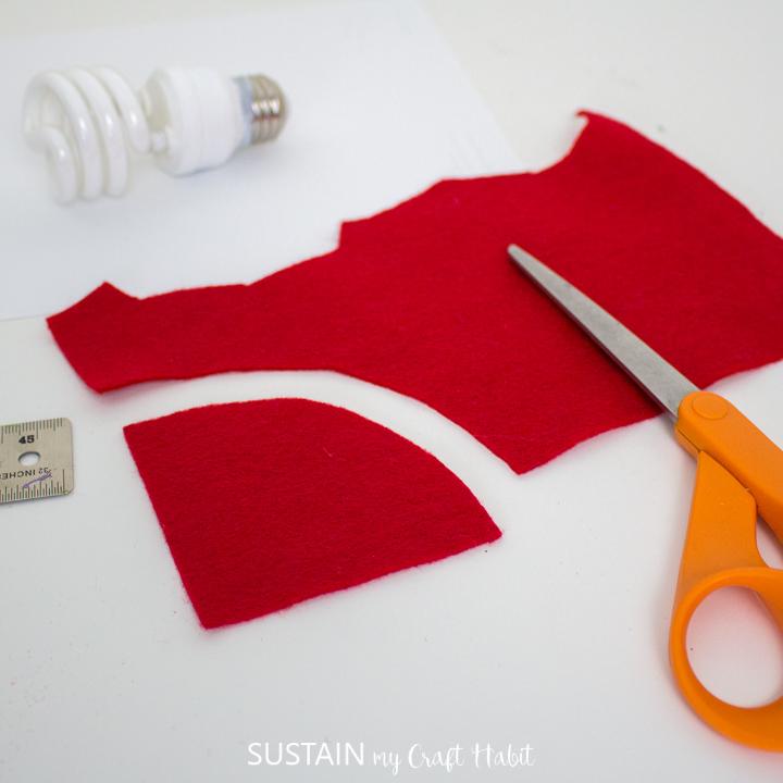 Cutting red felt fabric.