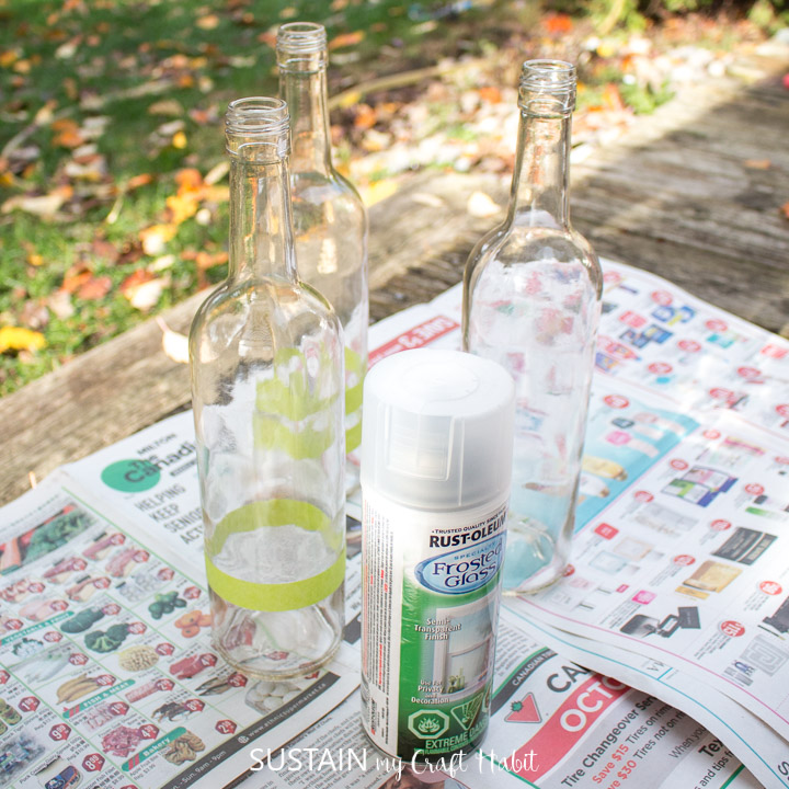 Arranging wine bottles on a protective surface with spray paint.