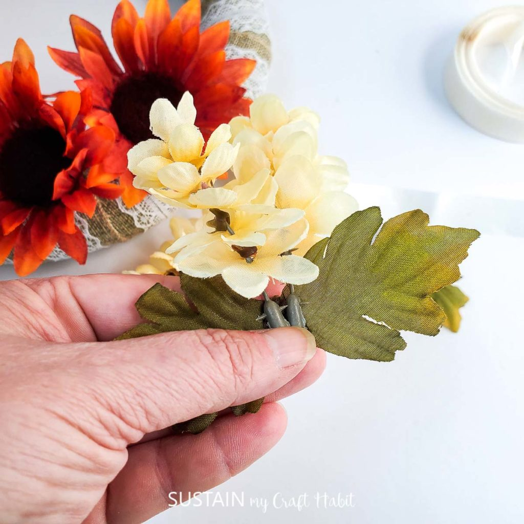 Removing plastic cream flowers from the stem.