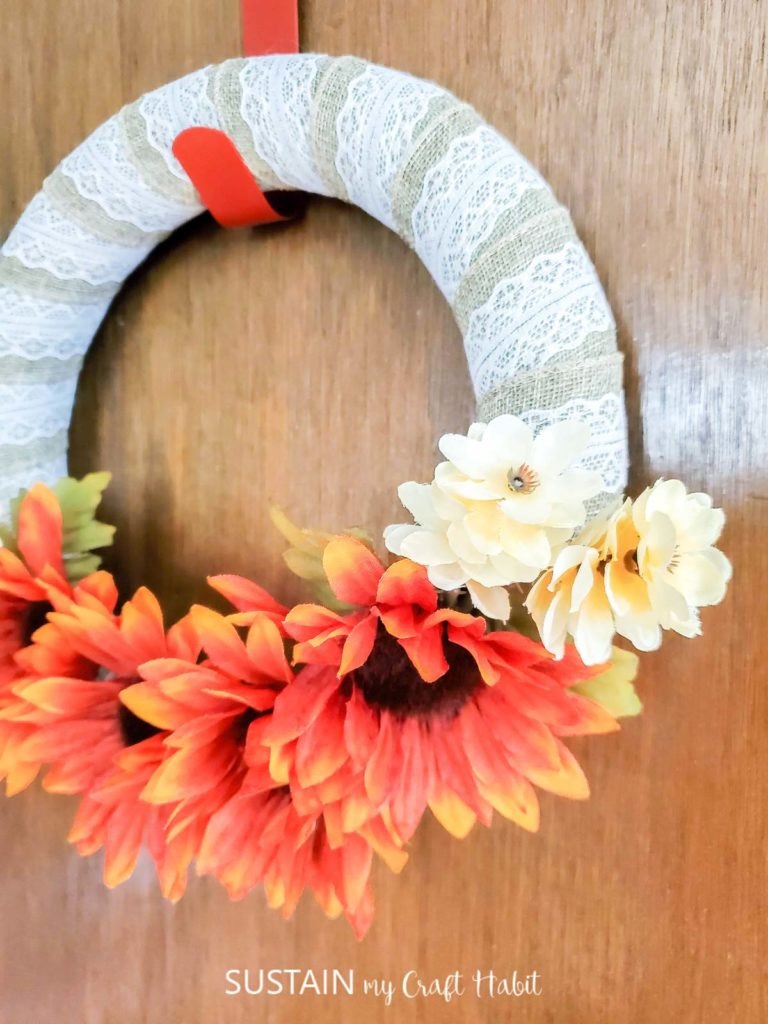 Dollar store fall wreath hung on a door.