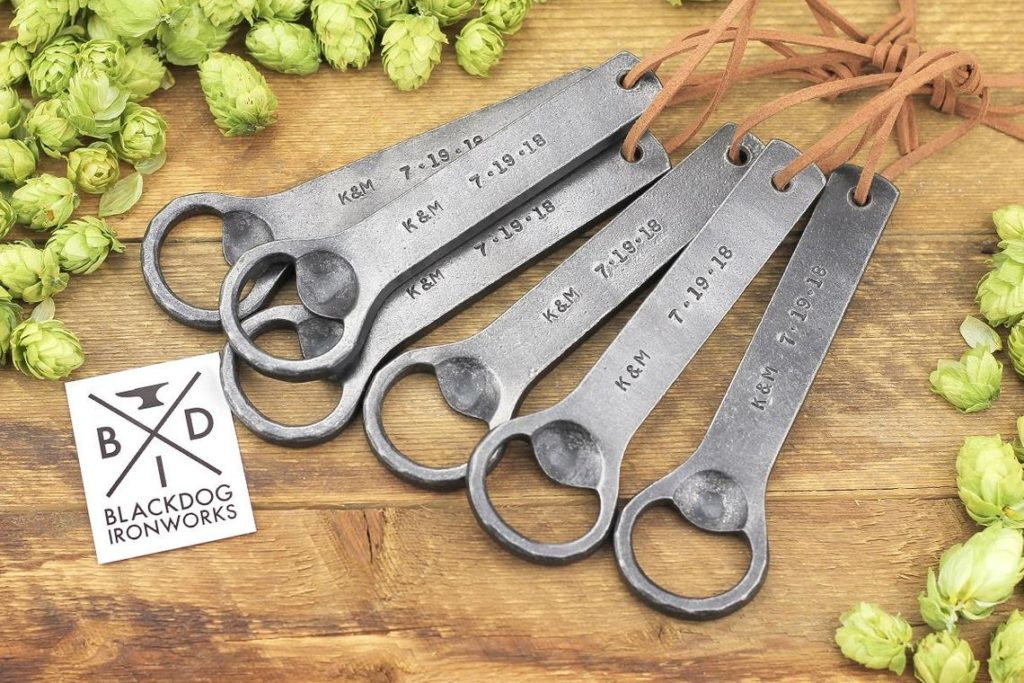 Six bottle openers placed on a wood tray.