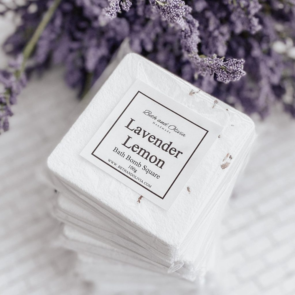 """Stacked squared bath bombs with """"lemon lavender"""" written on the front."""