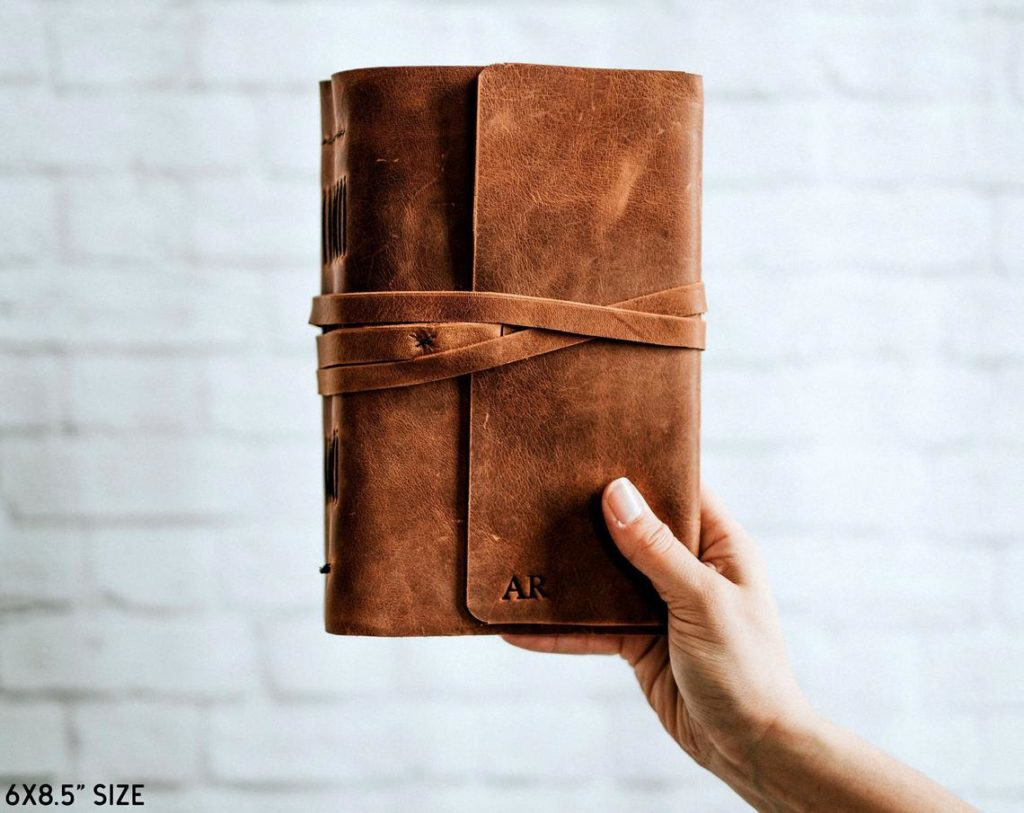 Holding a brown leather journal.
