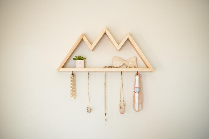 A wood shelf on the wall holding necklaces.