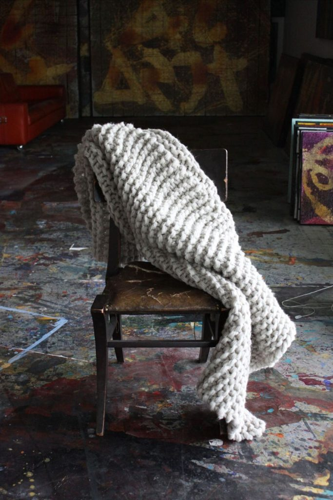 Chunky wool blanket placed on a chair.