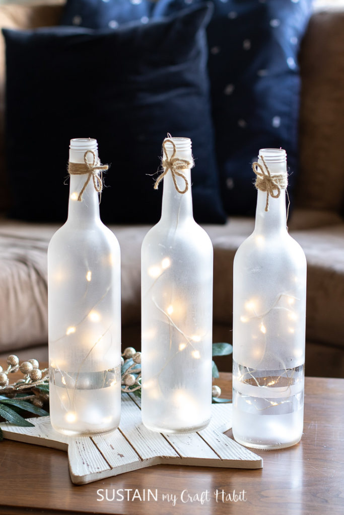 Frosted wine bottle centerpieces with twinkle lights.