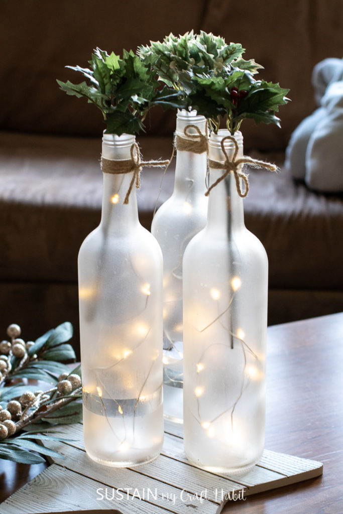 Frosted wine bottle centerpieces arranged with twinkle lights and fresh greenery.