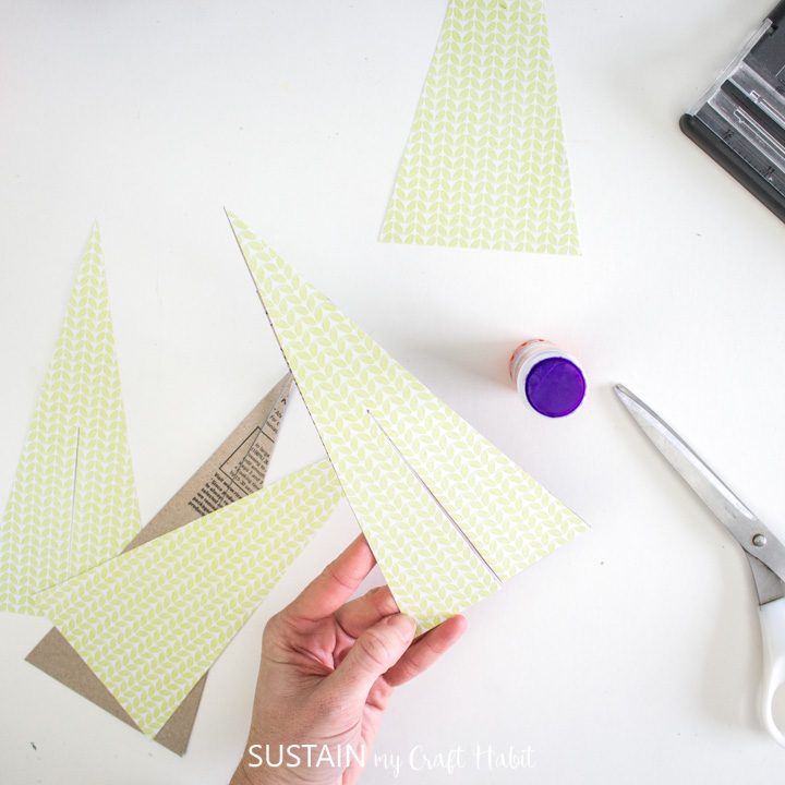 Gluing scrapbook paper onto the cardboard Christmas trees.